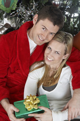 Portrait of a cheerful young couple with Christmas gift embracing
