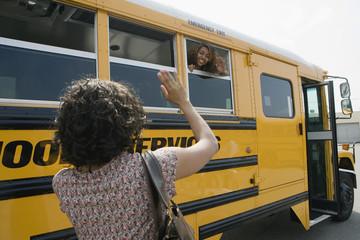 Mother waving goodbye to teenage daughter on School Bus