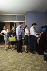 Impatient business people queuing at vending machine