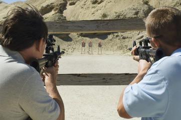 Rear view of two men aiming rifles at firing range during combat training