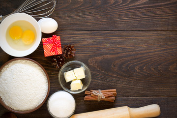 Baking ingredients for christmas cake with cinnamon on rustic wooden background.