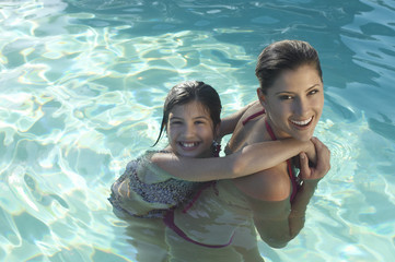 Portrait of a happy mother giving daughter piggy back in swimming pool