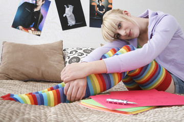Full length portrait of teenage girl smiling while sitting in bed