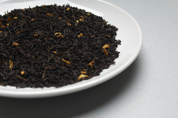 Closeup of dried tea leaves in a plate isolated over grey background