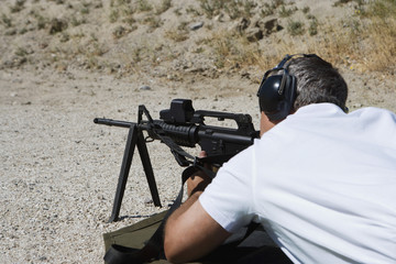 Man lying on ground aims machine gun at firing range