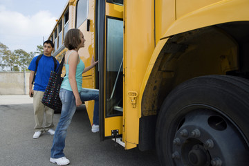 Young students getting in yellow school bus