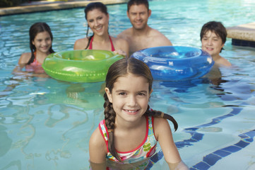 Portrait of a cute elementary girl in swimming pool with family in the background