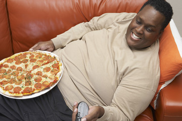 High angle view of an obese African American man watching television with pizza on lap