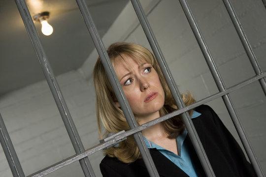 Caucasian criminal woman behind bars in jail
