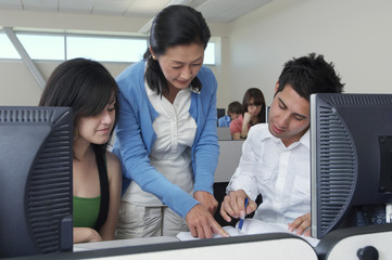 Teacher assisting students in computer class with classmates in the background