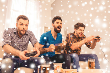 Excited  cheerful men play video game with beer on xmas holidays