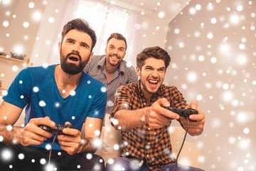 Three best happy friends playing video game on snowy background