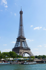 Eiffel Tower over Seine river waters at summer day, Paris, France