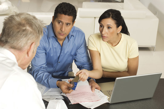 Couple giving documents and credit cards to financial advisor on a meeting