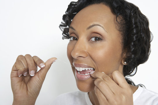 Closeup portrait of an African American woman flossing her teeth on white background