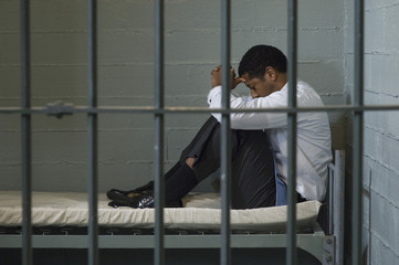 Depressed businessman sitting on bed behind the prison bars