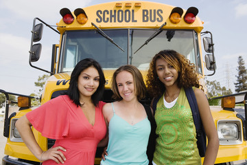 Portrait of pretty teenage girls standing together by school bus