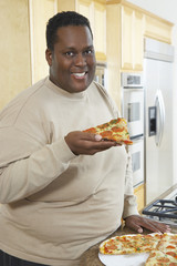 Portrait of an obese African American man holding slice of pizza at kitchen counter