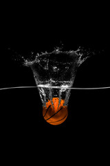 Basketball falls into the water on black background