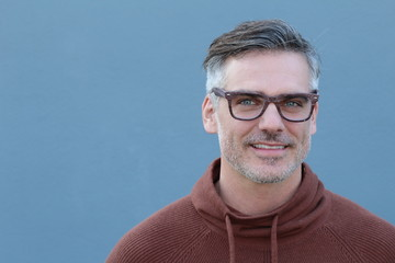 Close up Middle Age Man Wearing Brown Sweater and Eyeglasses Smiling at the Camera, Isolated on Blue Background with Copy Space