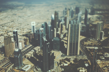 True tilt shift shooting from top of Dubai skyscrapers, residential buildings and highways on sunny summer day