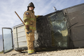 Full length of a firefighter with axe standing by a crashed car