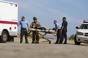 Police officer with firefighter and paramedics taking injured man in ambulance on stretcher