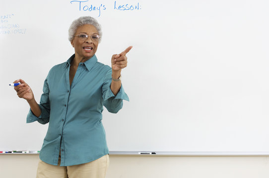 Senior teacher explaining during lecture with whiteboard in the background
