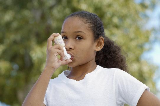 Closeup of a girl using asthma inhaler