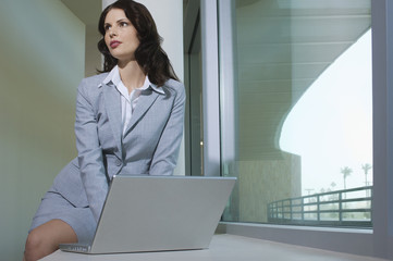 Beautiful young business woman using laptop sitting on window ledge