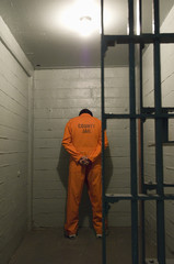 Prisoner standing against the wall in prison cell