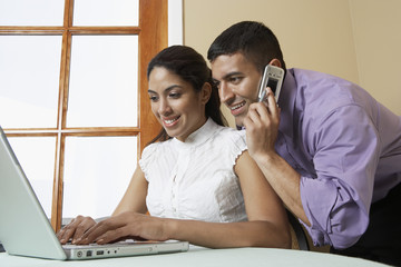 Business man and woman working with laptop at desk in office