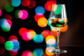 glass of white wine against a glowing bokeh - copy space, select