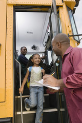 Elementary student looking at male teacher while getting down from school bus