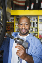 Portrait of an African American male mechanic working on a tire