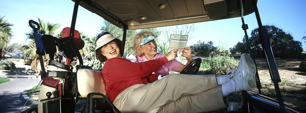 Two women laughing in golf cart with scorecard