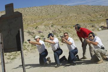 Full length of four people firing guns at shooting range
