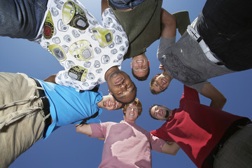 Group of multiethnic male friends forming huddle against blue sky