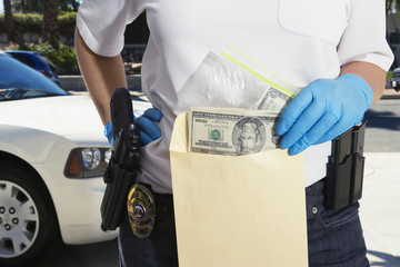 Midsection of a female police officer putting money in evidence envelope