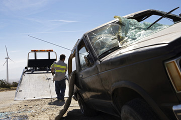 Rear view of a man preparing to lift crashed car onto tow truck