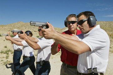 Instructor assisting officers with hand guns at firing range during weapons training