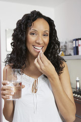 Portrait of happy African American woman taking pill with water at home