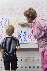 Female teacher explaining calendar to little boy in classroom