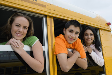 Portrait of high school students looking out from windows of a yellow school bus