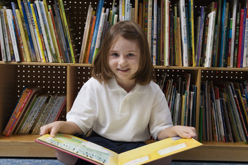 Portrait of a cute schoolgirl with picture book in school library