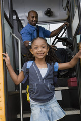 Portrait of a cute little girl getting off the school bus