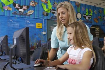 School girl using computer with teacher in classroom