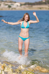 Girl with arms raised goes in sea