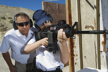 Instructor assisting woman aiming machine gun at firing range in desert