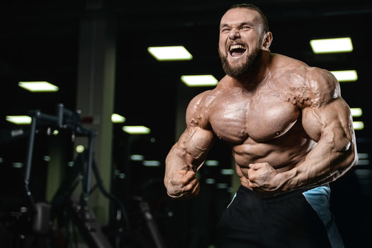 Brutal strong bodybuilder athletic men pumping up muscles with d